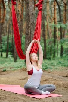 Het meisje houdt zich bezig met ademhalingsoefeningen in de natuur.