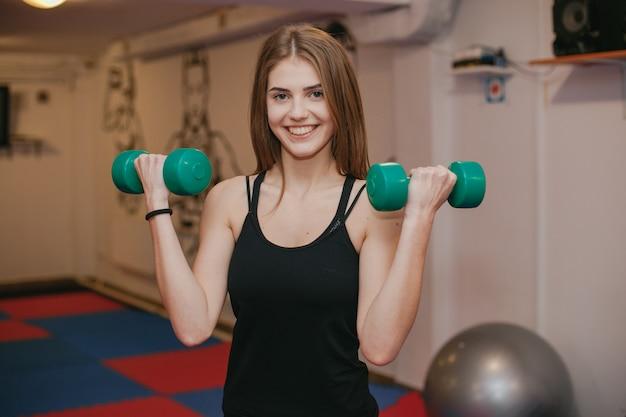 Het meisje houdt zich bezig met sporten in de sportschool