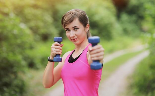 Het meisje houdt zich bezig met sporten met gewichten in het bos van de natuur. gezond fit leven