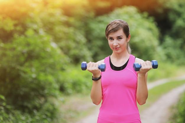 Het meisje houdt zich bezig met sporten met gewichten in het natuurbos. gezond fit leven