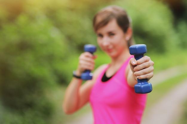 Het meisje houdt zich bezig met sporten met gewichten in het natuurlijke bos