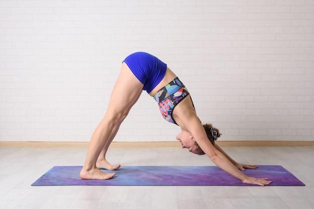 Het meisje houdt zich bezig met yoga. asana adho mukha shvanasana.