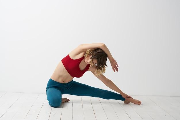 Het meisje houdt zich bezig met yoga tegen een lichte achtergrond