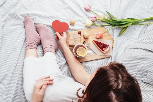 Het meisje in bed kreeg 's ochtends bloemen, cadeautjes en ontbijt op bed. gefeliciteerd met valentijnsdag.