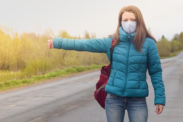 Het meisje in beschermend medisch gezichtsmasker vangt een auto op de weg. liftende, reizende jonge vrouw.