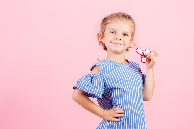 Het meisje in blauw gestript overhemd speelt in hand rode spinner