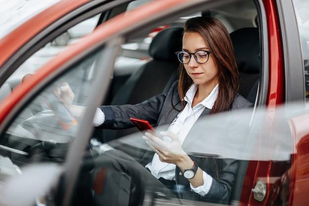 Het meisje in de auto achter het stuur kijkt naar de notificatietelefoon en leest het bericht