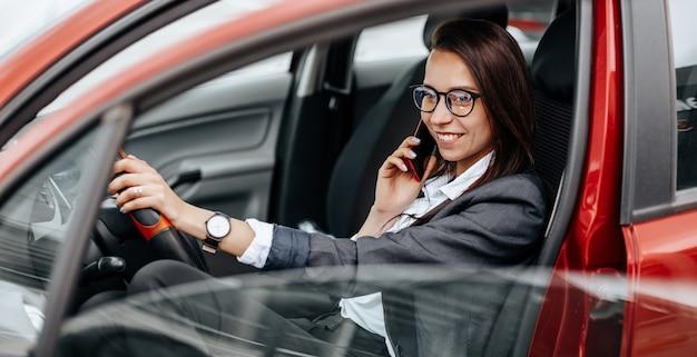 Het meisje in de auto achter het stuur kijkt naar de notificatietelefoon