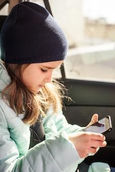Het meisje in de auto dat op een reis wacht of ouders die de telefoon of gadgets gebruiken