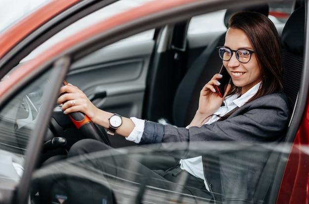 Het meisje in de auto praten aan de telefoon