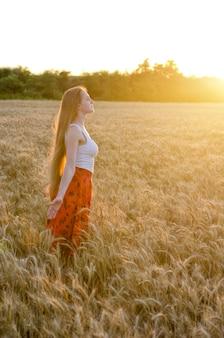 Het meisje in de bevindende wapens van het tarwegebied uitgestrekt bij zonsondergang en geniet in openlucht van