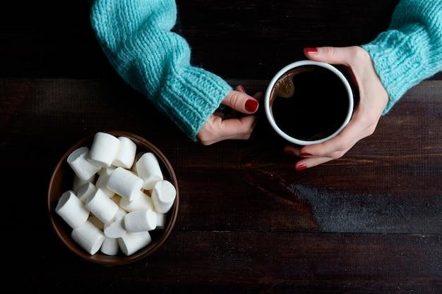 Het meisje in de blauwe kop van de sweaterholding van de close-upkom van koffiehanden overhandigt de ruimte van het heemstexemplaar