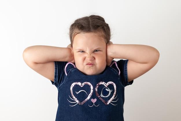 Het meisje in de blauwe spijkerjurk bedekte haar oren met haar handen, wil nergens naar luisteren