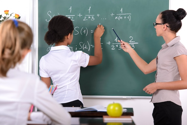 Het meisje in de buurt van het bord schrijft wiskundige vergelijkingen.