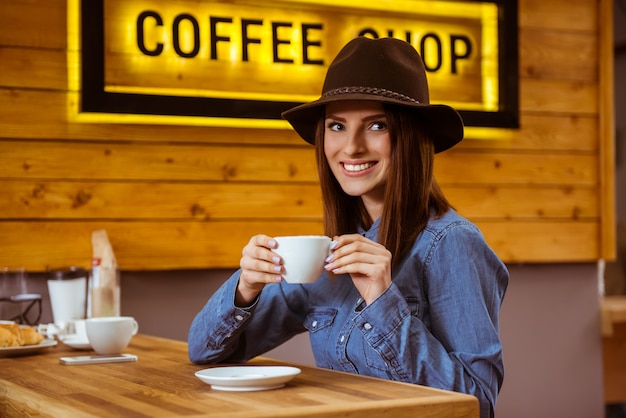 Het meisje in de dop drinkt koffie en glimlacht.