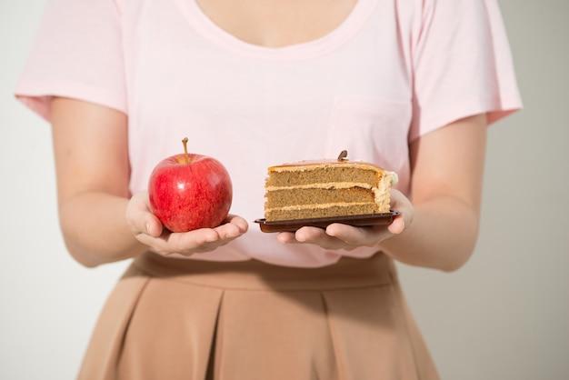 Het meisje in de ene hand heeft een appel, in de andere hand een taart.