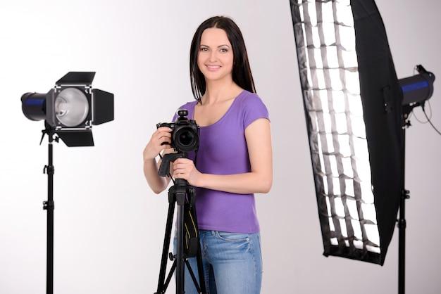Het meisje in de fotostudio werkt en glimlacht.