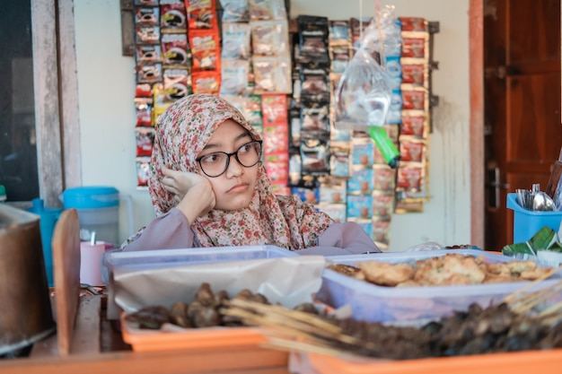 Het meisje in de hijab-kraamverkoper is verdrietig als de winkel leeg is van kopers in de wagenstalling