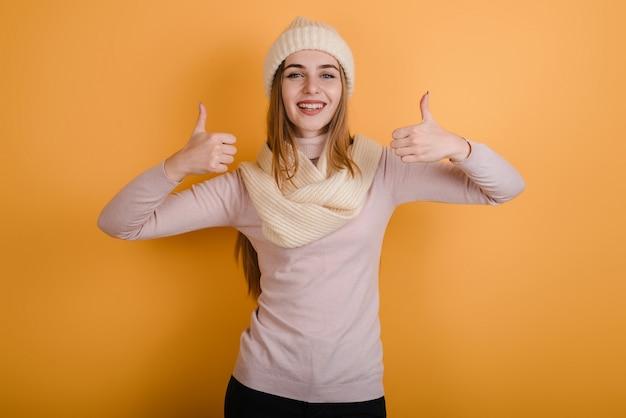 Het meisje in de hoed toont een gebaar van super. op een gele achtergrond