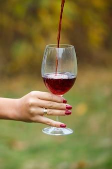 Het meisje in de jurk houdt een glas rode wijn vast in het herfstbos