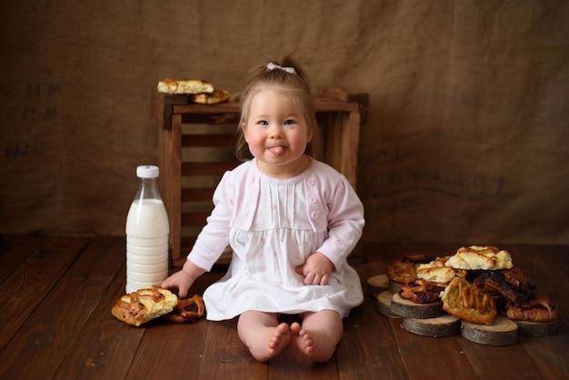 Het meisje in de keuken eet zoete gebakjes.