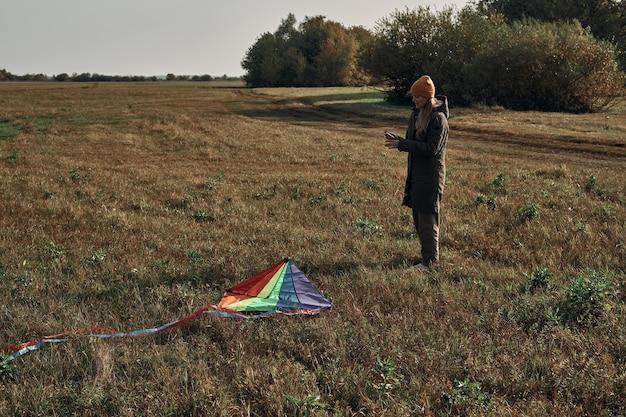 Het meisje in de natuur lanceert een vlieger. herfst weer.