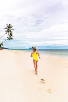 Het meisje in de rand in de vorm van kerstbomen en geel zwempak rent op het strand
