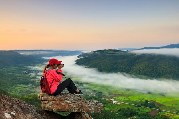 Het meisje in de rode jas staande op de berg