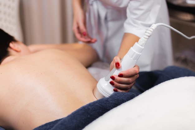 Het meisje in de spa-salon krijgt een rug- en nekmassage, ligt in de cosmetologietafel, ontspant en geniet van het proces