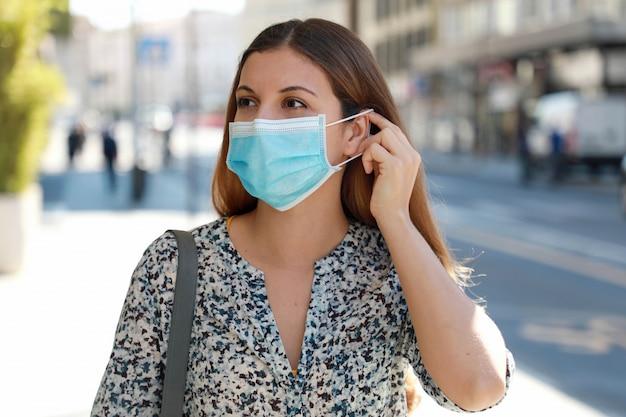 Het meisje in de straat zet een medisch masker op. jonge bedrijfsvrouw die chirurgisch masker draagt dat in stadsstraat loopt.