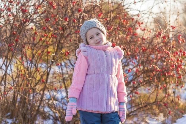 Het meisje in de winterkleren glimlacht