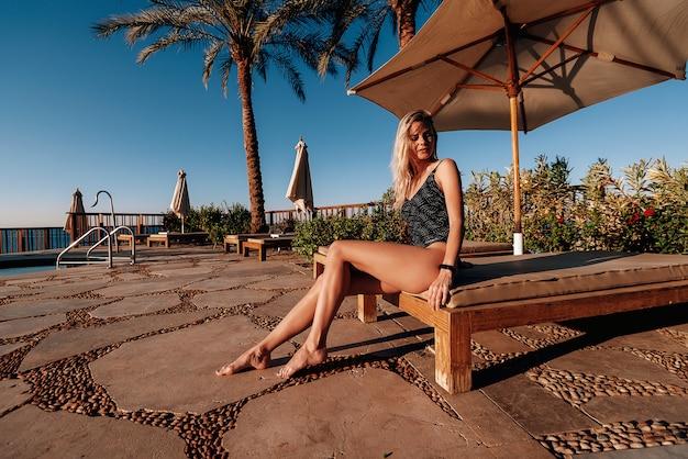 Het meisje in een badpak op het strand dichtbij het zwembad in de hete zon ontspant op vakantie