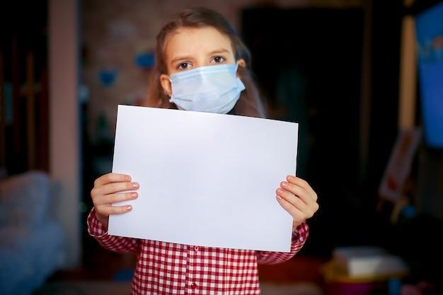 Het meisje in een beschermend maskerpyjama houdt een leeg blad vast