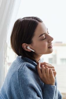 Het meisje in een blauwe sweater dichtbij de vensterhoofdtelefoons luistert naar muziek