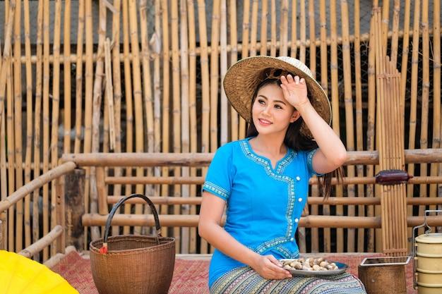 Het meisje in een blauwe traditionele thaise stijlkleding plukt paddestoelen om orden te verzenden