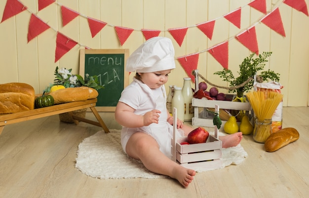 Het meisje in een chef-kokkostuum zit met fruit