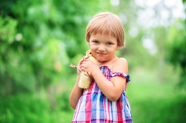 Het meisje in een de zomerzonnejurk koestert een eendje dat zich op aard in het gras bevindt