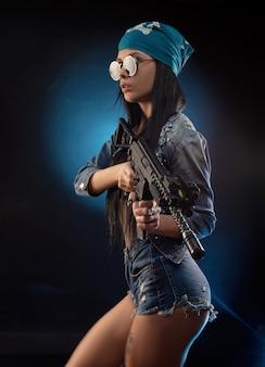 Het meisje in een denim jasje met een automatisch geweer