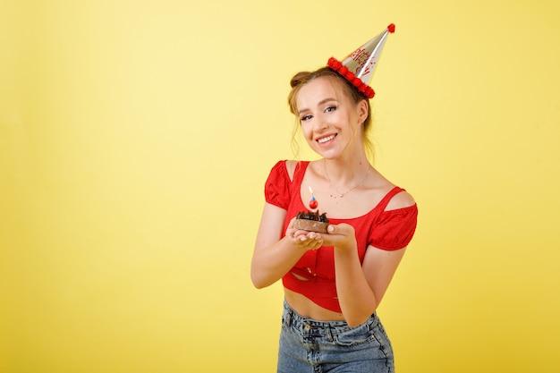 Het meisje in een glb viert verjaardag op een gele ruimte