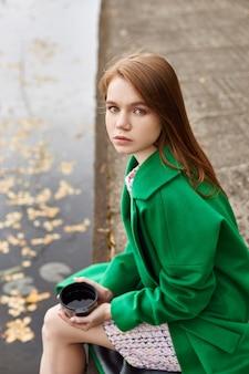Het meisje in een groene laag loopt langs de meerdijk