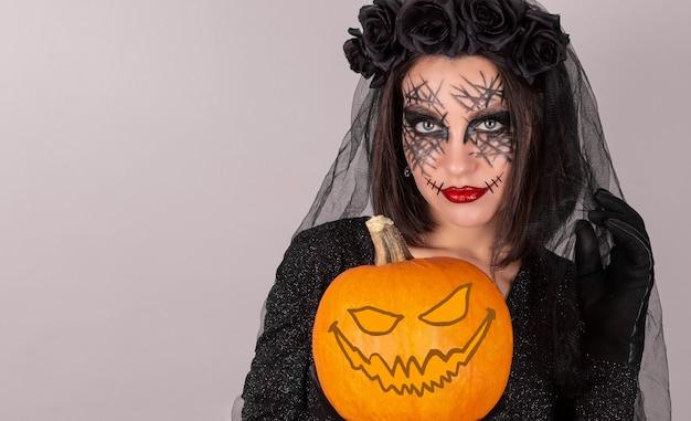 Het meisje in een halloweenkostuum met pompoen in haar handen
