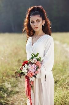 Het meisje in een lange kleding bevindt zich op een gebied met kroon op haar hoofd en boeket bloemen in haar handen, mooie vrouw