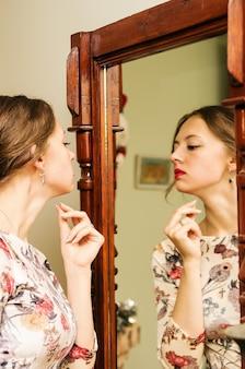 Het meisje in een mooie jurk kijkt in de spiegel