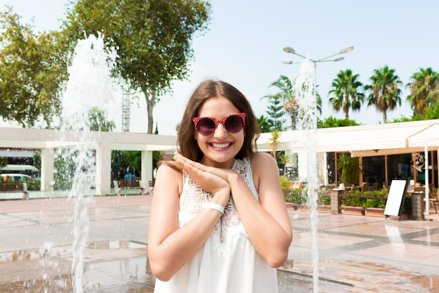 Het meisje in een nevel van water in een fonteinholding overhandigt dichtbij haar gezicht