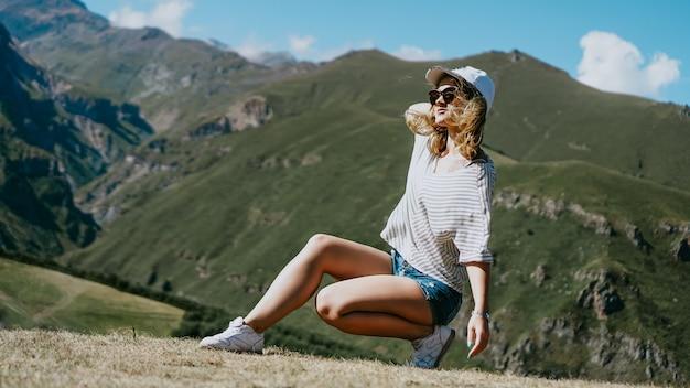 Het meisje in een pet en korte broek in de bergen zit op het gras