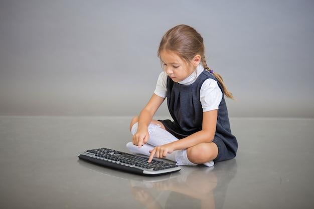 Het meisje in een schooluniform zit op een grijze achtergrond en drukt vanaf de computer op de toetsen op het toetsenbord