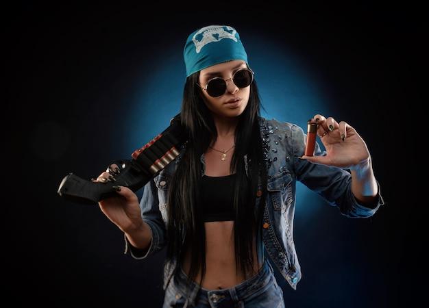 Het meisje in een spijkerjasje met een jachtgeweer