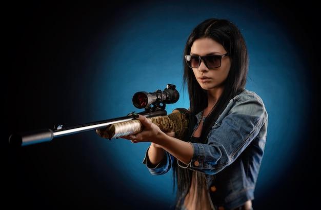 Het meisje in een spijkerjasje met een sluipschuttersgeweer
