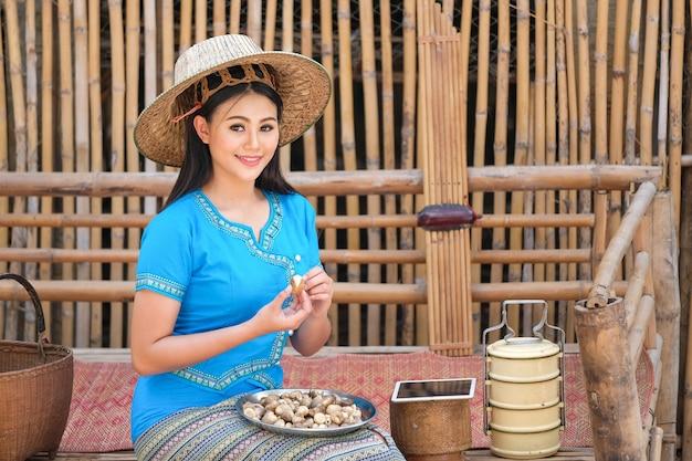 Het meisje in een traditionele thaise stijlkleding plukt paddestoelen om orden naar klanten te verzenden.