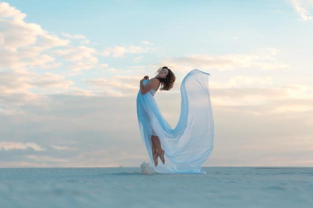 Het meisje in een vlieg witte kleding danst en stelt in het zand